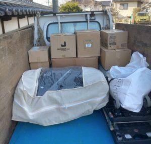 不用品の入った段ボール箱を軽トラックへ積んでおります。