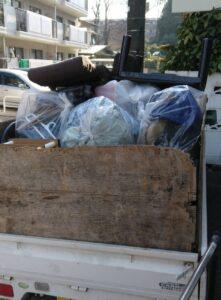 軽トラックへ袋に入った不用品を積んでおります。
