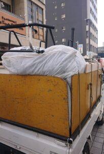 不用品を軽トラックへ積んでおります。